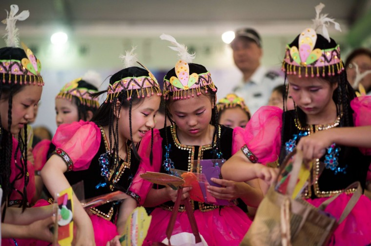 Young girls dressed in Inner Mongolian costumes prepare for a show during a tea promotion festival in a park in Shanghai on June 1, 2015, during International Children's Day. (AFP Photo/Johannes Eisele)
