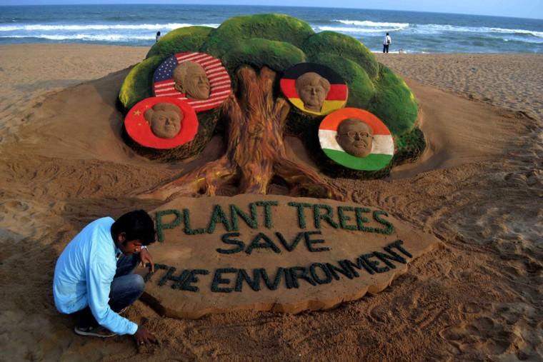 Indian sand artist Sudarsan Pattnaik gives the final touches to his sand sculpture featuring four top world leaders - Chinese President, (L), US President Barack Obama, (2L), German Chancellor Angela Merkel (2R) and Indian Prime Minister Narendra Modi amidst the branches of a tree on the eve of World Environment Day at Puri beach, some 65 kms from Bhubaneswar on June 4, 2015. (AFP Photo/Asit Kumara)