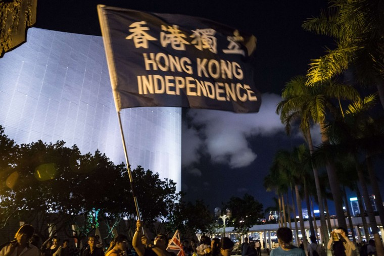 "A pro-democracy activist waves a flag that reads ""Hong Kong Independence"" during the commemoration of China's 1989 Tiananmen Square crackdown in the Tsim Sha Tsui district of Hong Kong on June 4, 2015. Tens of thousands were expected to mark the 26th anniversary of the Tiananmen Square crackown, organisers say, as they call on people to ""stay united"" as the city faces frustrations over its own democratic reforms. (AFP Photo/Anthony Wallace)"