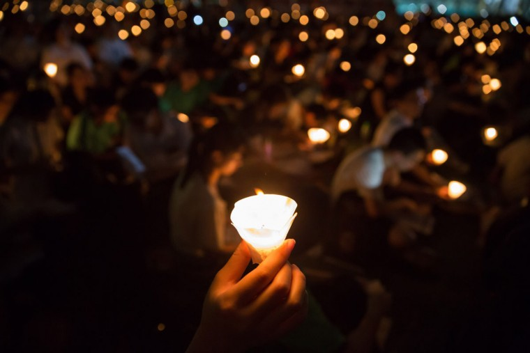 "People take part in a candlelight vigil in Hong Kong on June 4, 2015, to mark the crackdown on the pro-democracy movement in Beijing's Tiananmen Square in 1989. Tens of thousands were expected to mark the 26th anniversary of the Tiananmen Square crackdown, organisers said, as they call on people to ""stay united"" as the city faces frustrations over its own democratic reforms. (AFP Photo/Dale La reydale de la rey)"