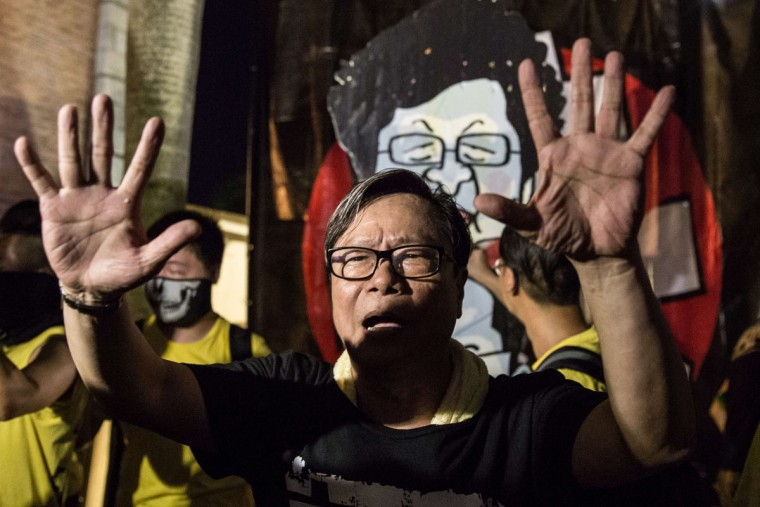 Lawmaker Raymond Wong (C) gestures for people to move back before the burning of a placard (back top) representing Carrie Lam by pro-democracy activists from the Civic Passion group during the commemoration of China's 1989 Tiananmen Square crackdown in the Tsim Sha Tsui district of Hong Kong late on June 4, 2015. Tens of thousands gathered to mark the 26th anniversary of China's Tiananmen Square crackdown, with the city deeply divided ahead of a vote on how to choose its next leader. (AFP Photo/Anthony Wallace)