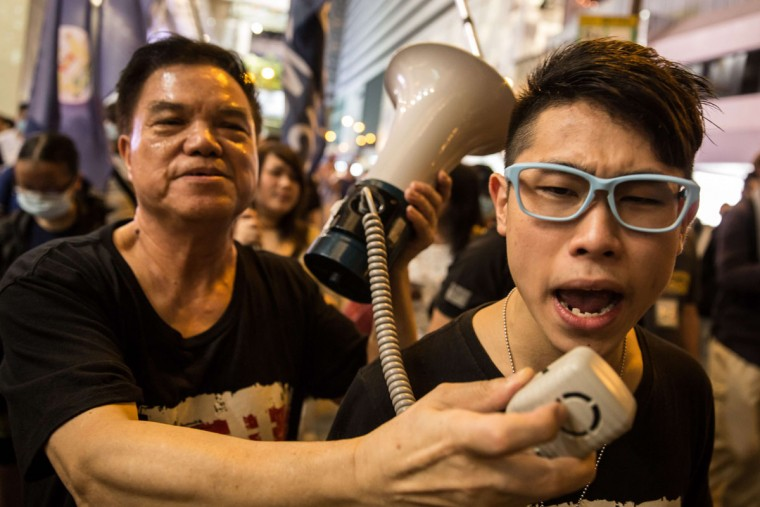 A pro-democracy activist (R) is provided with a megaphone as he shouts slogans while walking down a main road after the commemoration of China's 1989 Tiananmen Square crackdown in the Tsim Sha Tsui district of Hong Kong late on June 4, 2015. Tens of thousands gathered to mark the 26th anniversary of China's Tiananmen Square crackdown, with the city deeply divided ahead of a vote on how to choose its next leader. (AFP Photo/Anthony Wallace)