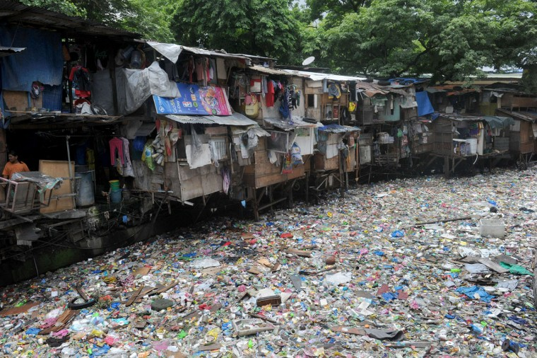 A row of shanty homes sits atop a sea of garbage on World Environment Day in Manila on June 5, 2015. Poverty and a lack of urban planning has been blamed for pollution in the Philippine capital city of 12 million people. (AFP Photo/Jay Directo)
