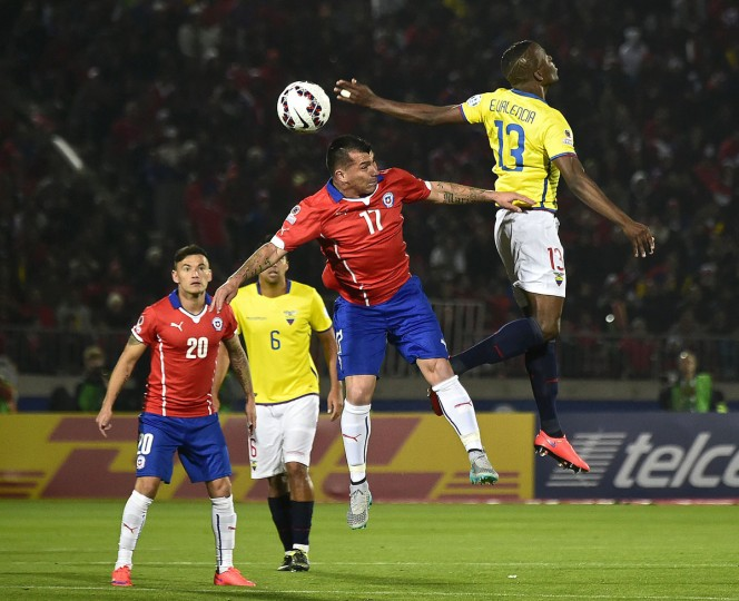 Chile's defender Gary Medel (C) vies for the ball with Ecuador's forward Enner Valencia (R) during the Copa America inauguration football match at the Nacional stadium in Santiago, on June 11, 2015. (AFP Photo/Luis Acosta)