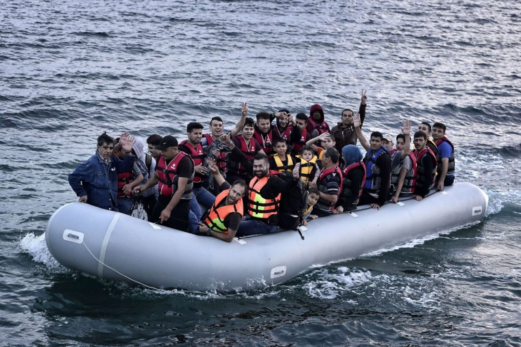 Syrian refugees flash the victory sign as they sit aboard a dinghy carrying heading to the island of Lesbos early on June 18, 2015. (LOUISA GOULIAMAKI/AFP/Getty Images)