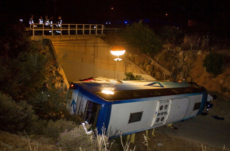 Rescue workers stand on a bridge above an overturned bus off the highway A2 near Albufeira, in the early hours on June 18, 2014 after skidded off the road and down an embankment killing three Dutch tourists and injuring another 31. (MIGUEL FERREIRA/AFP/Getty Images)