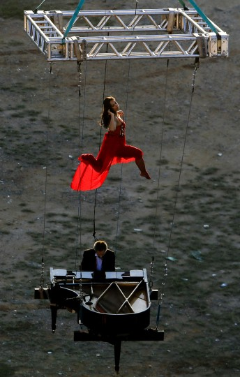 "Brazilian pianist Ricardo de Castro Monteiro and a ballerina perform in the air with a piano hanging from wires during the annual ""Virada Cultural"" event, in Sao Paulo, Brazil, on June 21, 2015. (Miguel Schincariol/AFP/Getty Images)"