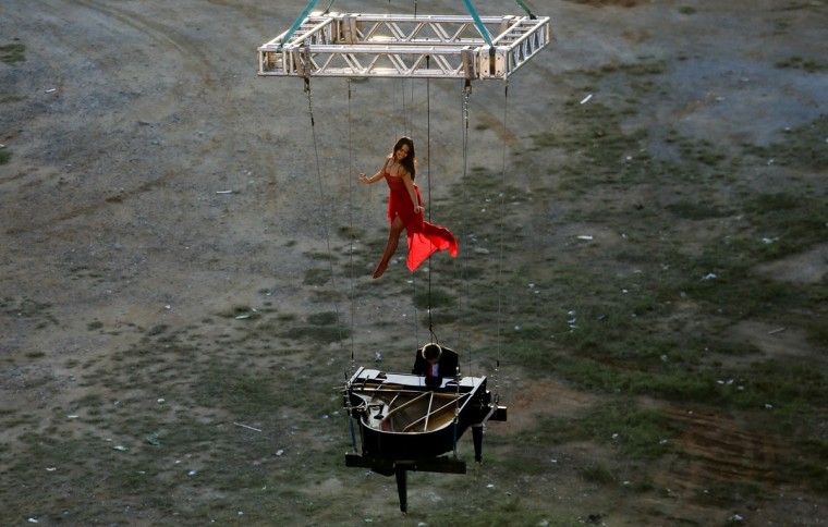 "Brazilian pianist Ricardo de Castro Monteiro and a ballerina play in the air with a piano hanging from wires during the annual ""Virada Cultural"" event, in Sao Paulo, Brazil, on June 21, 2015. (Miguel Schincariol/AFP/Getty Images)"