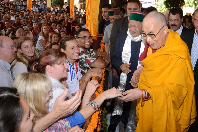 Tibetan Spiritual leader the Dalai Lama (R) is accompanied by The Chief Minister of the northern Indian state of Himachal Pradesh Virbhadra Singh (C), as he greets foreign students during an event to celebrate his 80th birthday at Tsuglakhang Temple in McLeod Ganj on June 22, 2015. The Dalai Lama marked his official 80th birthday on June 21, with prayers and celebrations at his hometown in exile but little to show for decades of lobbying for greater Tibetan autonomy. (AFP Photo/Narinder Nanu)