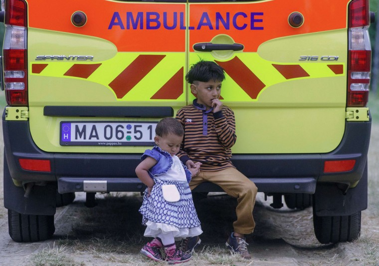 Migrant children sit on an ambulance during a check up by the local police officials nearby Szeged town at the Hungarian-Serbian border on June 24, 2015 during their patrol. (ABA SEGESVARI/AFP/Getty Images)