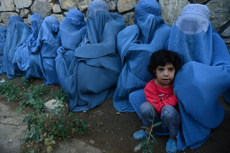 Afghan women wait with a child to get food from distribution scheme held during Ramadan in Herat on June 23, 2015. (Aref Karimi/AFP/Getty Images)