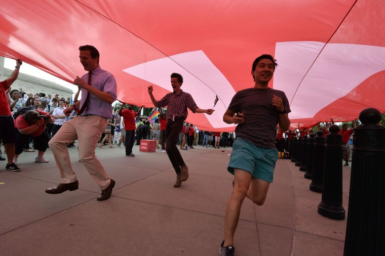 People run under a giant equality flag as they celebrate outside the Supreme Court in Washington, DC on June 26, 2015 after its historic decision on gay marriage. The US Supreme Court ruled Friday that gay marriage is a nationwide right, a landmark decision in one of the most keenly awaited announcements in decades and sparking scenes of jubilation. The nation's highest court, in a narrow 5-4 decision, said the US Constitution requires all states to carry out and recognize marriage between people of the same sex. (AFP Photo/P / )