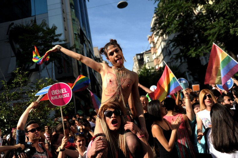 "People shout slogans and wave rainbow flags during the Gay Pride parade on June 28, 2015 in the Cihangir neighborhood near the Taksim square in Istanbul. Riot police in Istanbul used tear gas and water cannon to disperse thousands of participants in the Gay Pride parade in the Turkish city, an AFP reporter said. Police took action against the crowd when demonstrators began shouting slogans accusing the social conservative President Recep Tayyip Erdogan of ""fascism"". (Ozan Kose/AFP/Getty Images)"