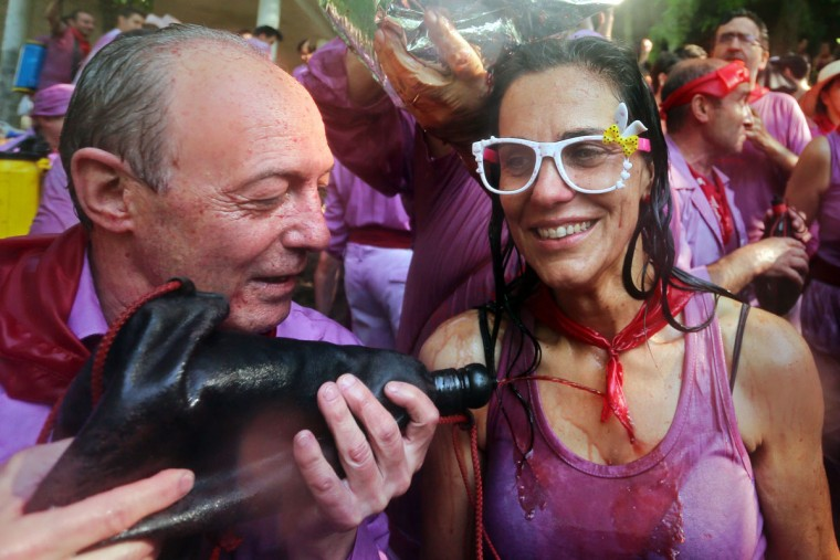 "A man uses a wineskine to pour red wine on a woman's chest during the""Batalla del Vino"" (Battle of Wine) in Haro, on June 29, 2015. (CESAR MANSO/AFP/Getty Images)"