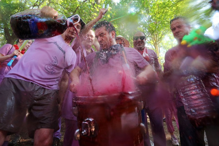 """Revelers pour red wine on a drum during the """"Batalla del Vino"""" (Battle of Wine) in Haro, on June 29, 2015. (CESAR MANSO/AFP/Getty Images)"""