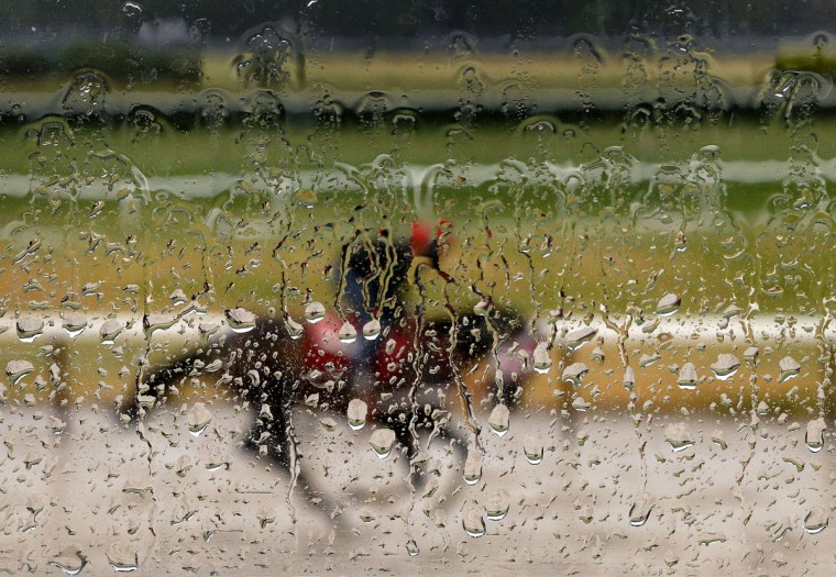 Rain water coats the window of an observation tower as an exercise rider guides a horse around the main track at Belmont Park, Tuesday, June 2, 2015, in Elmont, N.Y. Kentucky Derby and Preakness Stakes winner American Pharoah will try for a Triple Crown Saturday, June 6, in the Belmont Stakes horse race (AP Photo/Julie Jacobson, File)