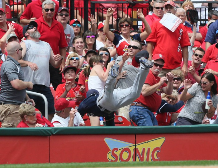 Milwaukee Brewers third baseman Hector Gomez flips into the stands while chasing a foul ball off the bat of St. Louis Cardinals' Jason Heyward during the sixth inning of a baseball game in St. Louis. (Chris Lee/St. Louis Post-Dispatch via AP)