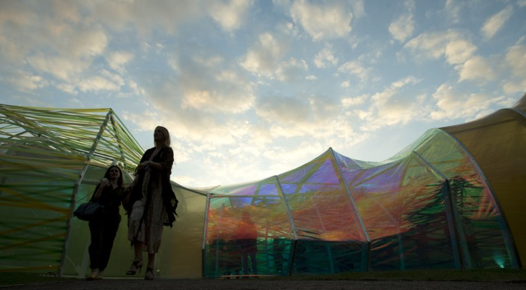 Invited guests walk around the outside of the Serpentine Pavilion 2015, in Hyde park London, Tuesday, June 23, 2015. Designed by Spanish architect group Selgascano- which was formed in 1998 by Jose Selgas and Lucia Cano, the pavilion is open to the public from June 25 to October 18. The architects' work is characterized by the use of synthetic materials and new technologies, with their belief that architecture is secondary to nature. (AP Photo/Alastair Grant)