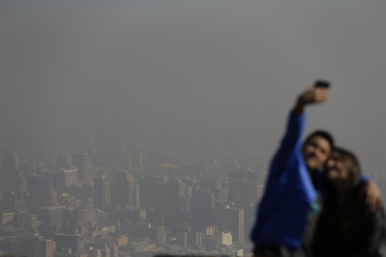 "Tourists take pictures of themselves from the ""Cerro San Cristobal"" with a view behind them of smog filled downtown Santiago, Chile, Monday, June 22, 2015. Authorities declared an environmental emergency Monday because of high levels of pollution in the air. (AP Photo/Jorge Saenz)"