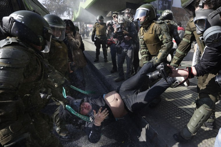 A protester is detained by riot police at the end of a march in Santiago, Chile, Thursday, June 25, 2015. Teachers and students are asking for better salaries and participation in the government's education reform, and the march ended with some incidents between groups of hooded or masked protesters and police. (AP Photo/Jorge Saenz)