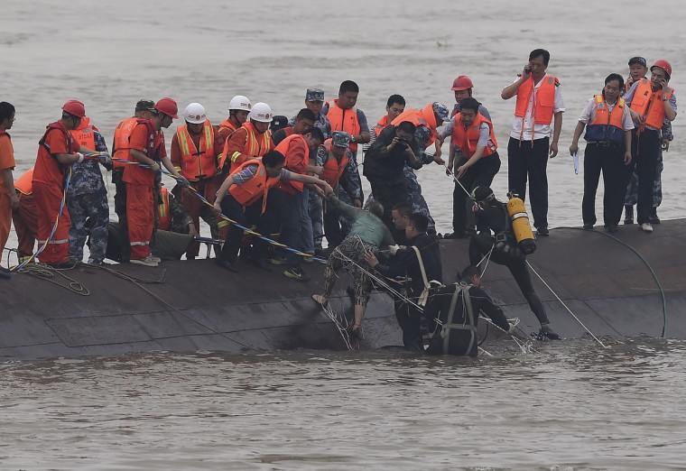 In this photo released by China's Xinhua News Agency, rescuers save a survivor, center, from the overturned passenger ship in the Jianli section of the Yangtze River in central China's Hubei Province Tuesday, June 2, 2015. Rescuers pulled several survivors to safety after hearing cries for help Tuesday from inside a capsized cruise ship that went down overnight in a storm on China's Yangtze River, state broadcaster CCTV said. (Cheng Min/Xinhua via AP)