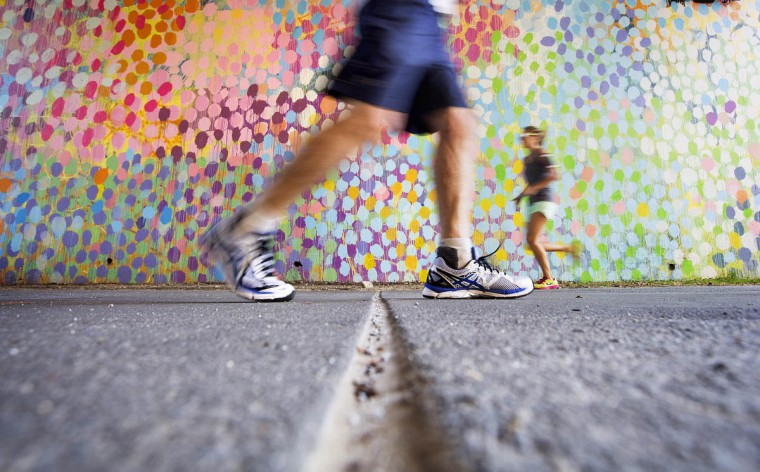 Joggers run past a painted mural along the BeltLine in Atlanta. Today marks National Running Day, celebrated annually on the first Wednesday in June. National Running Day was created in 2009 by some of the county's biggest running clubs and organizations to draw attention to the benefits of the activity. (David Goldman/AP photo)
