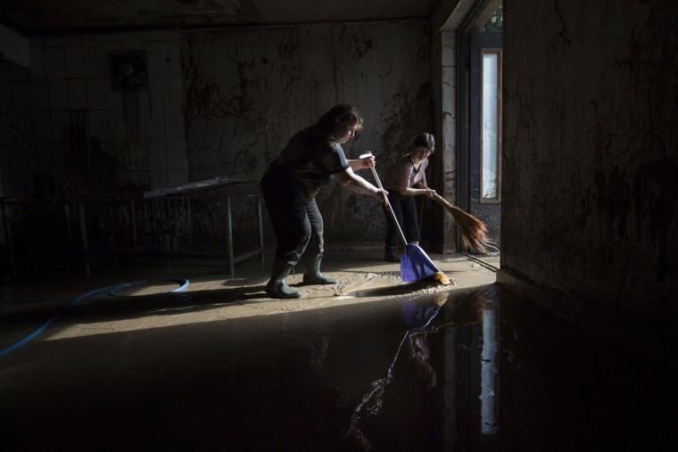 Volunteers clean a flat after Sunday's flooding in Tbilisi, Georgia, Monday, June 15, 2015. Workers and volunteers labored Monday in a flood-ravaged area of the Georgian capital to help victims while nervously watching for traces of dangerous animals that may have escaped the city zoo when it was inundated by the surging waters. Officials in the ex-Soviet republic said 14 people were confirmed dead. (AP Photo/Pavel Golovkin)