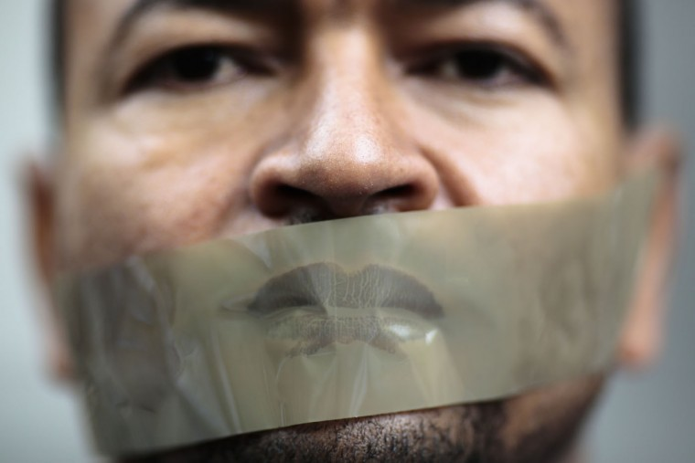 A man with tape on his mouth attends a demonstration in front of a court to support Ahmed Mansour in Berlin, Germany, Monday, June 22, 2015. Ahmed Mansour, 52, a senior journalist with the Qatar-based broadcaster Al-Jazeera, was detained at Tegel airport on Saturday on an Egyptian arrest warrant, Al-Jazeera said. (AP Photo/Markus Schreiber)