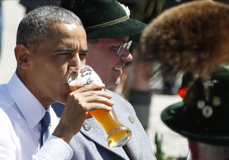 U.S. President Barack Obama drinks a beer as he sits between men dressed in traditional Bavarian clothes during a visit to the village of Kruen, southern Germany, Sunday, June 7, 2015 prior to the G-7 summit in Schloss Elmau hotel near Garmisch-Partenkirchen where the summit will start later the day. (AP Photo/Markus Schreiber)