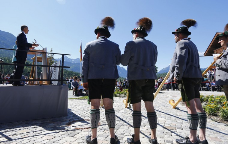 Alp horn players listen to a brief speech of U.S. President Barack Obama, left, during a visit to the village of Kruen, southern Germany, Sunday, June 7, 2015 prior to the G-7 summit in Schloss Elmau hotel near Garmisch-Partenkirchen where the summit will start later the day. (AP Photo/Matthias Schrader, pool)