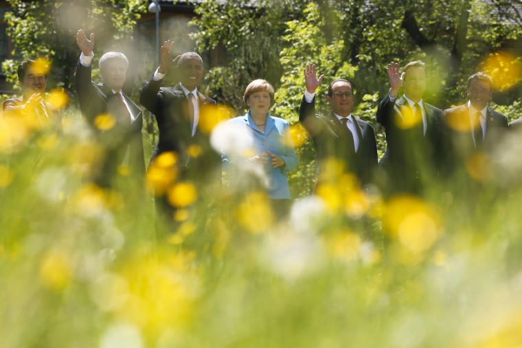 With flowers in the fore ground the G-7 leaders from left, Japanese Prime Minister Shinzo Abe, Canadian Prime Minister Stephen Harper, U.S. President Barack Obama, German Chancellor Angela Merkel, French President Francois Hollande, British Prime Minister David Cameron and Italian Prime Minister Matteo Renzi wave as they pose for a group photo during the G-7 summit at Schloss Elmau hotel near Garmisch-Partenkirchen, southern Germany, Sunday, June 7, 2015. (AP Photo/Markus Schreiber)
