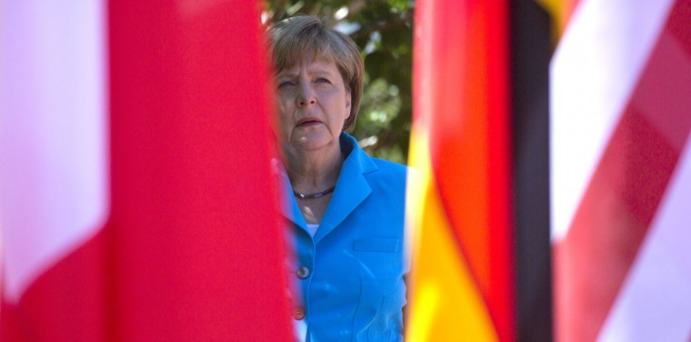 German Chancellor Angela Merkel waits near flags in the shade for G-7 leaders during arrivals for the G-7 summit at Schloss Elmau hotel near Garmisch-Partenkirchen, southern Germany, Sunday, June 7, 2015. The two-day summit will address such issues as climate change, poverty and the situation in Ukraine. (AP Photo/Virginia Mayo)