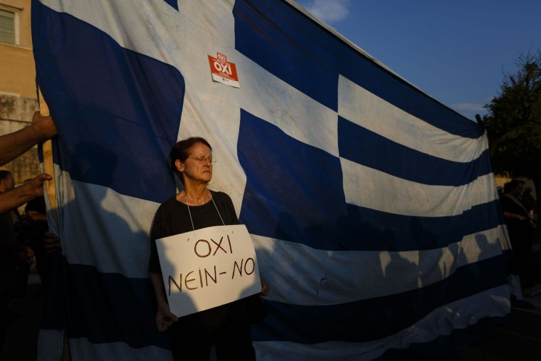 "A supporter of the NO vote in the upcoming referendum wears a sign reading 'No"" in Greek, German and English, as she stands next to a representation of the Greek national flag, during a rally at Syntagma square in Athens on Monday, June 29, 2015. Anxious Greek pensioners swarmed closed bank branches and long lines snaked outside ATMs as Greeks endured the first day of serious controls on their daily economic lives ahead of a July 5 referendum that could determine whether the country has to ditch the euro currency and return to the drachma. (AP Photo/Daniel Ochoa de Olza)"