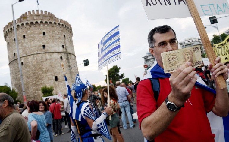 A supporter of the NO vote in the upcoming referendum, holds an old 1,000 drachma bank note during a rally in the northern Greek port city of Thessaloniki, Monday, June 29, 2015. Anxious Greek pensioners swarmed closed bank branches and long lines snaked at ATMs as Greeks endured the first day of serious controls on their daily economic lives ahead of a July 5 referendum that could determine whether the country has to ditch the euro currency and return to the drachma. (AP Photo/Giannis Papanikos)