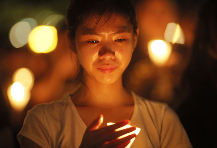 A woman holds a candlelight as people attend a candlelight vigil at Victoria Park in Hong Kong Thursday, June 4, 2015. Tens of thousands of Hong Kongers joined the candlelight vigil Thursday night marking the crushing of the 1989 student-led Tiananmen Square protests, an annual commemoration that takes on greater meaning for the city's young after last autumn's pro-democracy demonstrations sharpened their sense of unease with Beijing. (AP Photo/Vincent Yu)