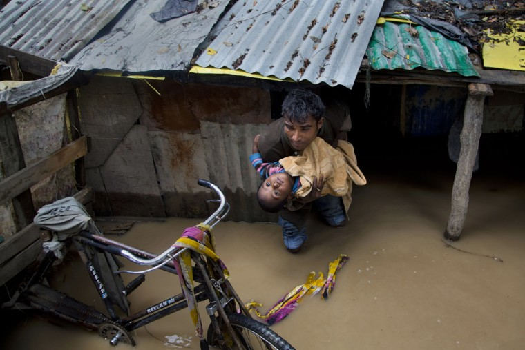 An Indian man carries a boy to move to a safer place after their neighborhood was flooded in Srinagar, Indian controlled Kashmir, Thursday, June 25, 2015. Authorities advised people living in low-lying areas to shift to safer places Thursday as rain-swollen rivers swamped several parts of the disputed Himalayan region. (AP Photo/Dar Yasin)