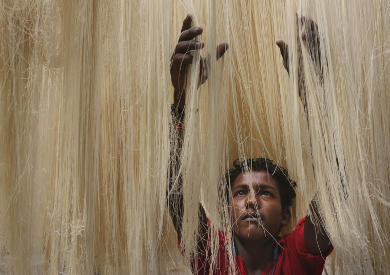 An Indian worker dries vermicelli, used to make a traditional sweet dish popular during the Islamic holy month of Ramadan, in Hyderabad, India, Thursday, June 25, 2015. Muslims throughout the world are marking the month of Ramadan, the holiest month in the Islamic calendar during which devotees fast from dawn till dusk. (AP Photo/Mahesh Kumar A.)