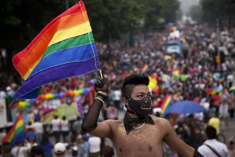 A reveler waves a rainbow flag during a gay pride parade in Mexico City, Saturday, June 27, 2015. Thousands of people marched down Paseo de la Reforma for one of the largest gay pride events in Latin America. (AP Photo/Marco Ugarte)