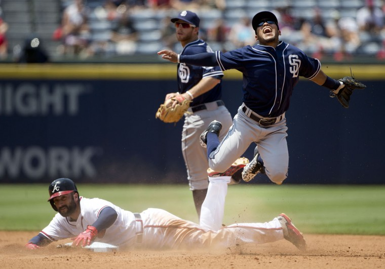 San Diego Padres shortstop Alexi Amarista, top right, is up ended by Atlanta Braves' Nick Markakis, bottom, as he turns a double play on a Juan Uribe ground ball in the sixth inning of a baseball game, Thursday, June 11, 2015, in Atlanta. (AP Photo/John Bazemore)