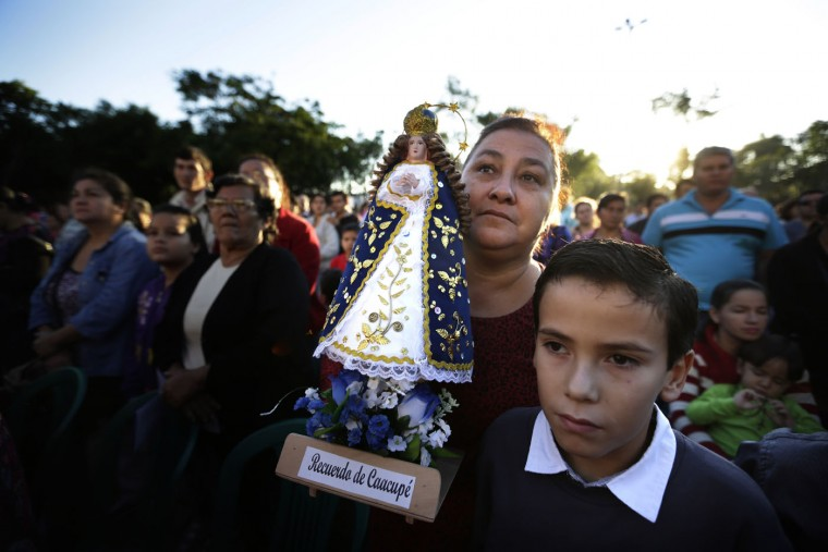 Mercedes Adad carries a Caacupe Virgin replica as she and her son Oscar participate of Corpus Christi mass in Caacupe, Paraguay, Sunday, June 7, 2015. Catholics take part in a procession through the streets of a neighborhood near their parish following mass and pray and sing celebrating the tradition and belief in the body and blood of Jesus Christ. (AP Photo/Jorge Saenz)