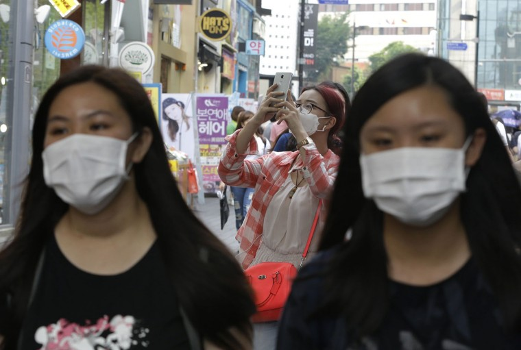 A foreign tourist, center, wears a mask as a precaution against Middle East Respiratory Syndrome (MERS) as she takes pictures with her smartphone at the Myeongdong, one of the main shopping districts, in Seoul, South Korea, Monday, June 8, 2015. South Korea on Monday reported its sixth death from MERS as authorities were bolstering measures to stem the spread of the virus that has left dozens of people infected. (AP Photo/Ahn Young-joon)