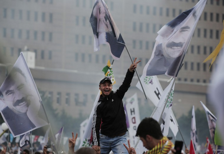 A supporter of the pro-Kurdish Peoples' Democratic Party, (HDP) flashes the V-sign as others wave flags of imprisoned Kurdish rebel leader Abdullah Ocalan, during a rally in Istanbul, Turkey, Monday, June 8, 2015, a day after the elections. The biggest change from Turkey's previous parliament is the ascendancy of the People's Democratic Party, a socially liberal force rooted in the Kurdish nationalism of Turkey's southeast. It attracted more than 12 percent of votes, breaching the minimum threshold of 10 percent. Turkey's President Recep Tayyip Erdogan's long-ruling Justice and Development Party (AKP), has suffered surprisingly strong losses in parliament that will force it to seek a coalition partner for the next government. (AP Photo/Lefteris Pitarakis)
