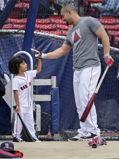 Boston Red Sox right fielder Shane Victorino gets a high-five from his son, Kingston Shane Victorino, during batting practice before the first baseball game of a doubleheader against the Minnesota Twins at Fenway Park in Boston. Victorino has been on the disabled list since May 24, with a left calf strain. (Charles Krupa/AP photo)