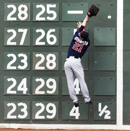 Minnesota Twins left fielder Shane Robinson leaps but can't make the catch on a double by Boston Red Sox designated hitter David Ortiz during the third inning in the first baseball game of a doubleheader at Fenway Park in Boston. (Charles Krupa/AP photo)