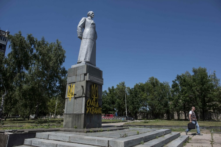 "A local resident walks past a monument to KGB founder Felix Dzerzhinsky, with Ukrainian emblem and the words ""Glory to Ukraine"" painted on it, in Dzerzhinsk, eastern Ukraine, Monday, June 8, 2015. Obama says the Group of Seven leading nations stand behind Ukraine and agree that economic sanctions should remain in place against Russia until it fully implements a cease-fire with Ukraine that has been violated repeatedly. (AP Photo/Evgeniy Maloletka)"