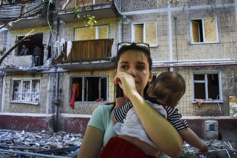 A woman cries as she holds her baby, near to her house damaged by shelling, in Horlivka, eastern Ukraine, Thursday, June 11, 2015. At least four people including a child were killed by shelling in east Ukraine on Thursday. (AP Photo/Mstyslav Chernov)