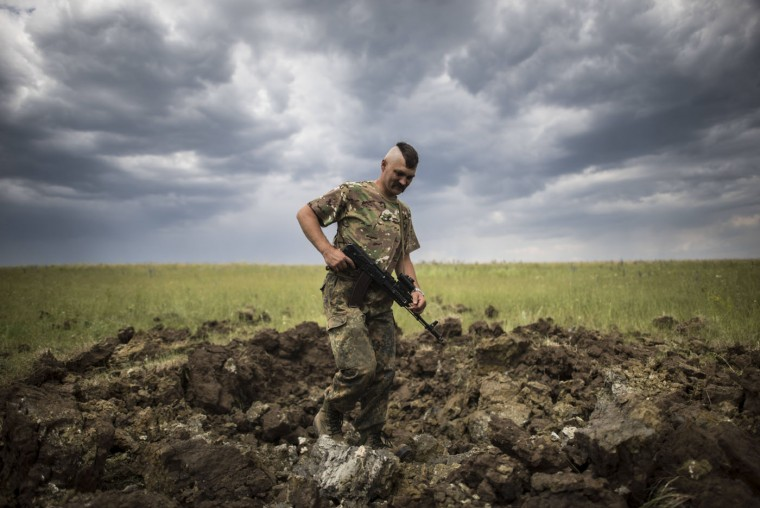 A Ukrainian serviceman investigates a crater left by a Grad rocket in the village of Toshkivka, Luhansk region, eastern Ukraine, Monday, June 15, 2015. (AP Photo/Evgeniy Maloletka)