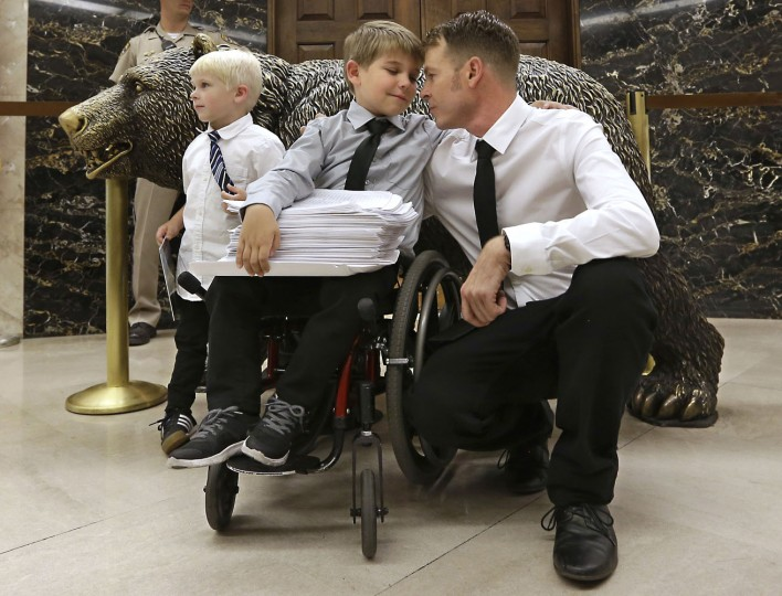 Otto Coleman, 6, waits outside the Governor's office with his brother Fenton, 4, left, and father Joshua, to deliver a stack of petitions with thousands of signatures calling on California Gov. Jerry Brown to veto a measure requiring nearly all California school children to be vaccinated Monday, June 29, 2015, in Sacramento, Calif. The state Senate approved the bill sending it to Brown. Joshua Coleman said his son has been wheelchair bound as a result of an adverse reaction to a vaccine. (AP Photo/Rich Pedroncelli)