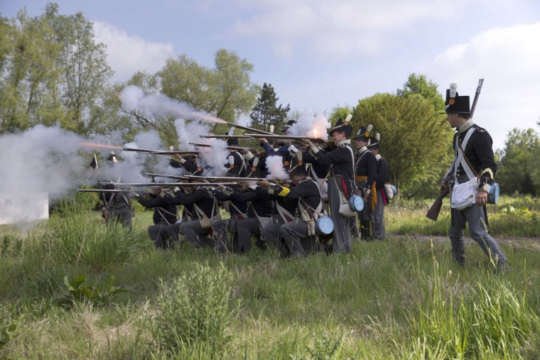 In this May 10, 2015, photo, historical re-enactors dressed as soldiers of the Belgian-Dutch 7th Battalion of the Line fire their weapons during a drill at a Napoleonic era living history camp in Elewijt, Belgium. The Belgian-Dutch living history group is coordinating their group for participation in the 200th anniversary of the Battle of Waterloo which will take place in June 2015. (AP Photo/Virginia Mayo)