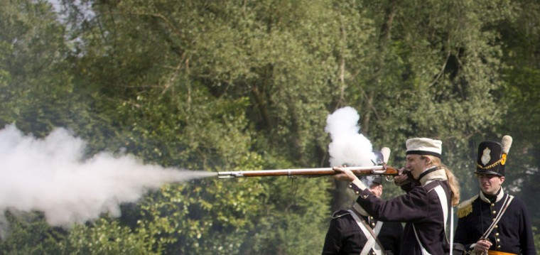 In this May 10, 2015, photo, the youngest member of a re-enactor group of the Belgian-Dutch 7th Battalion of the Line, Luca Scalzotto, 19, fires his weapon during a drill at a Napoleonic era living history camp in Elewijt, Belgium. The Belgian-Dutch living history group is coordinating their group for participation in the 200th anniversary of the Battle of Waterloo which will take place in June 2015. (AP Photo/Virginia Mayo)
